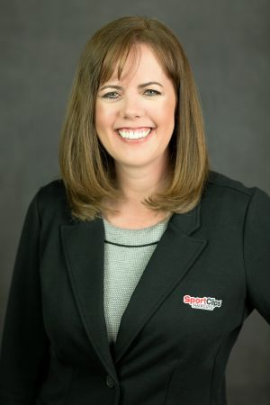 Headshot of franchisee Debra Sawyer in black coat with Sport Clips logo on left breast