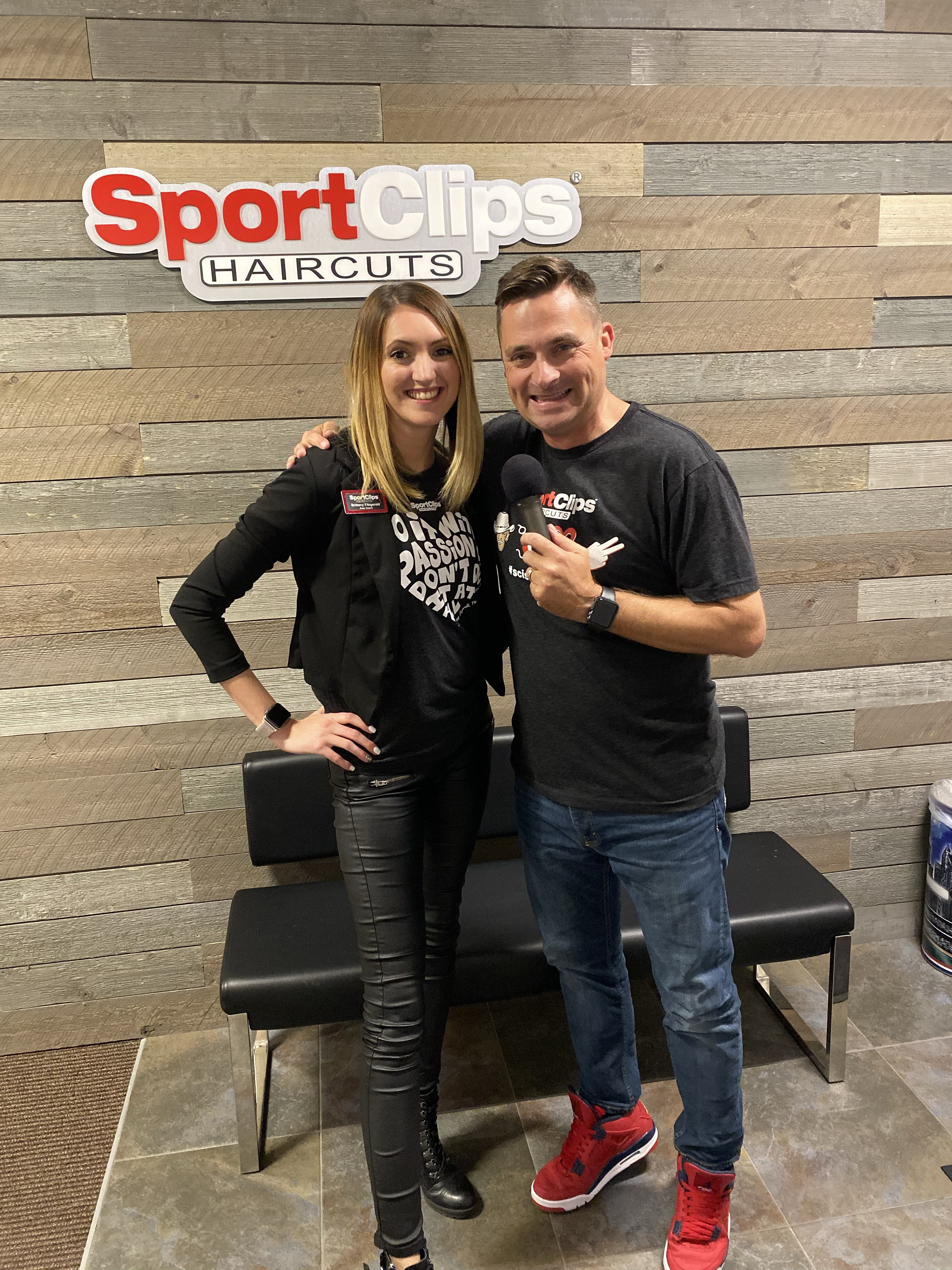 Man and woman standing in front of Sport Clips sign holding a microphone