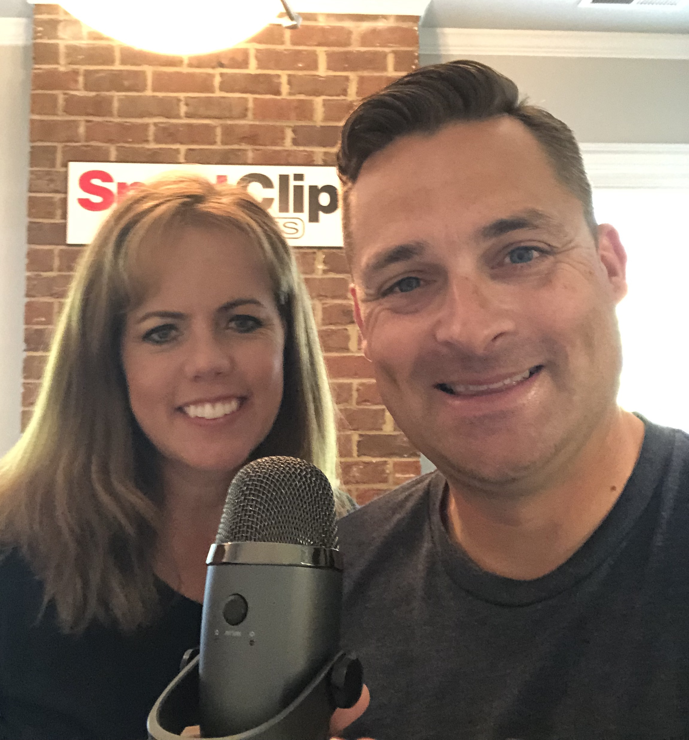 Chad Jordan and Debra Sawyer holding a microphone