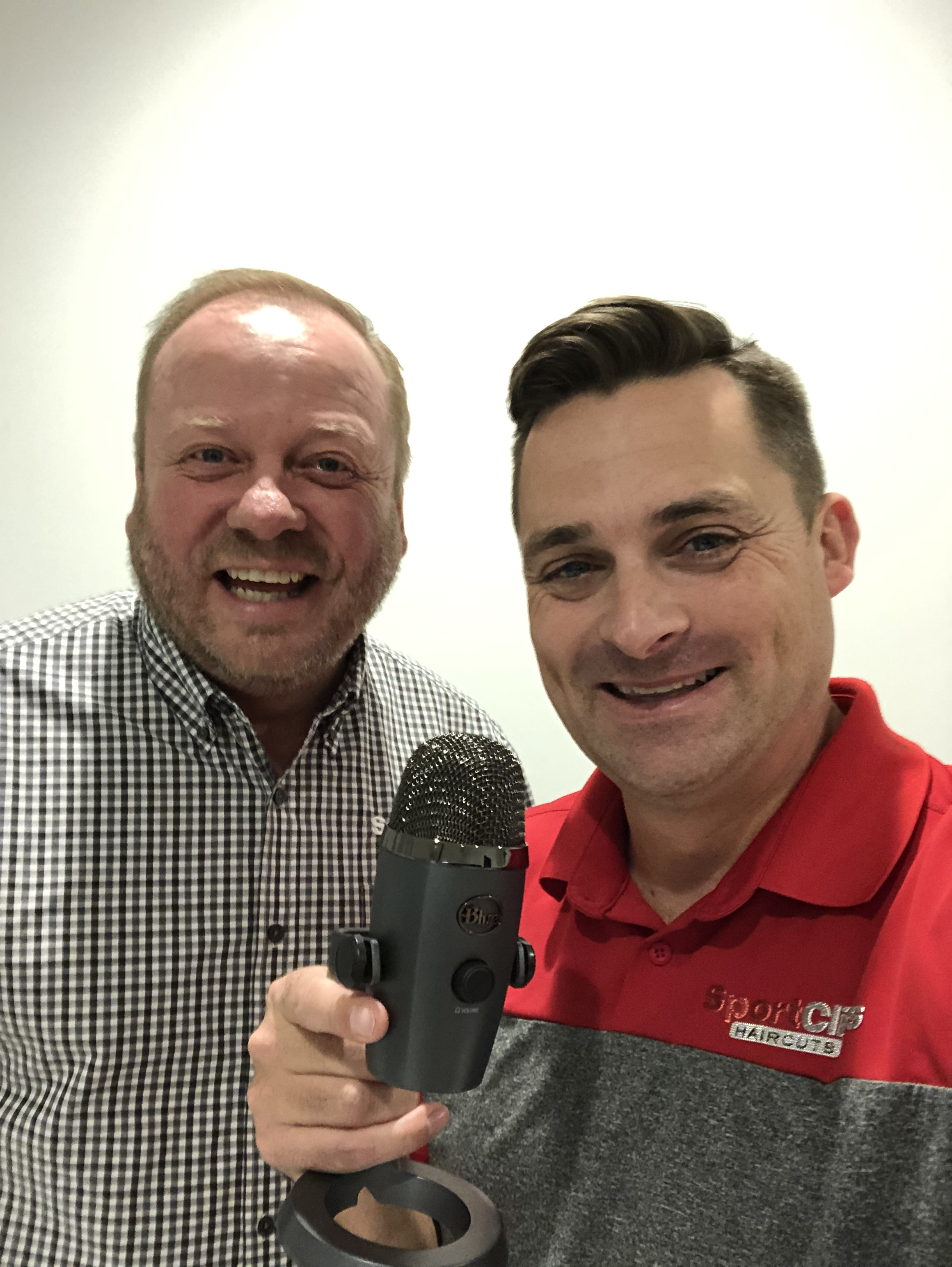 Duke Sorensen and Chad Jordan holding a microphone for their podcast