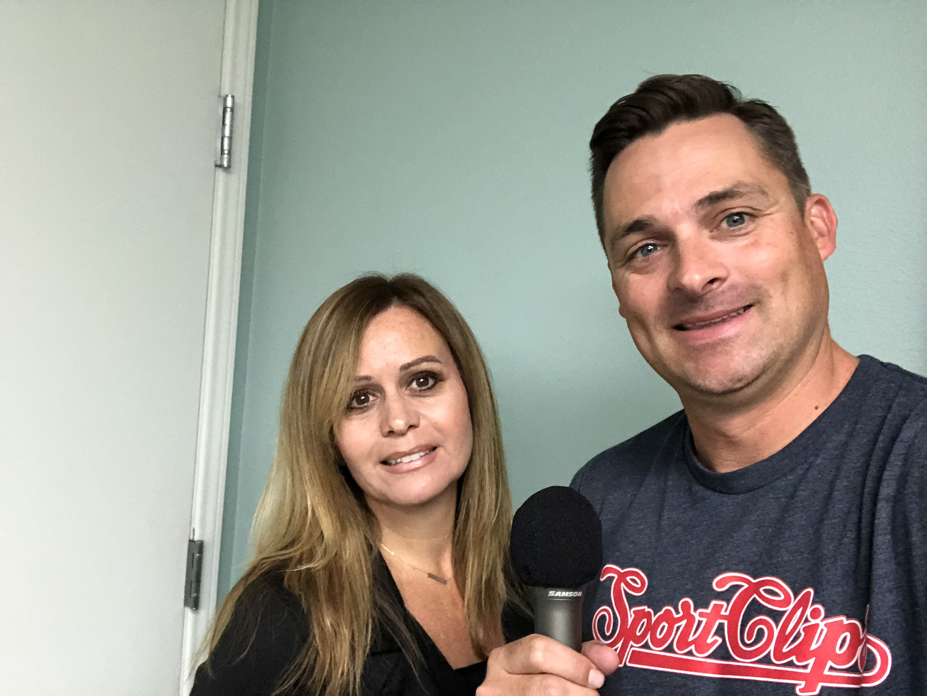 Jennifer Justis and Chad Jordan holding a microphone