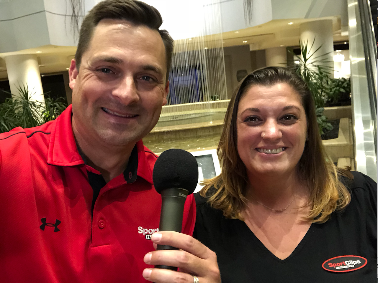 Chad Jordan and Meghan Blanchette holding a microphone in front of a water fountain
