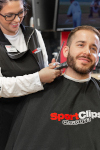 Sport Clips stylist with scissors and mask